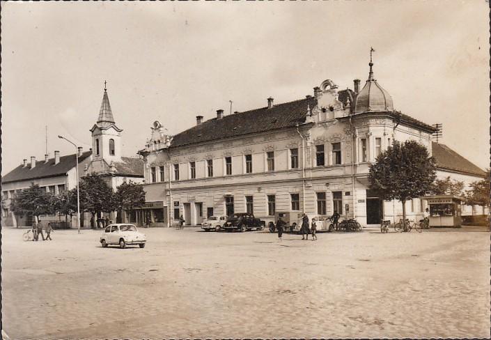 Na staroj fotografiji s druge polovine 20. veka vidi se centar Stare Pazove, automobili, hotel Srem, ljudi, filijalna katolička crkva  itd.