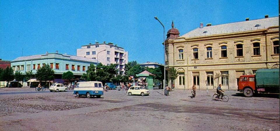 Na staroj fotografiji s druge polovine 20. veka vidi se centar Stare Pazove, zgrada nekadašnje štedionice iz 1905.god., ljudi, automobili itd.