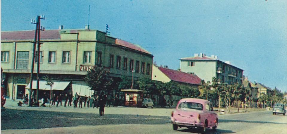Na staroj fotografiji s druge polovine 20. veka vidi se centar Stare Pazove, ljudi, automobili, kombi, sa leve strane je zelena zgrada nekadašnjeg Cetrotekstila.