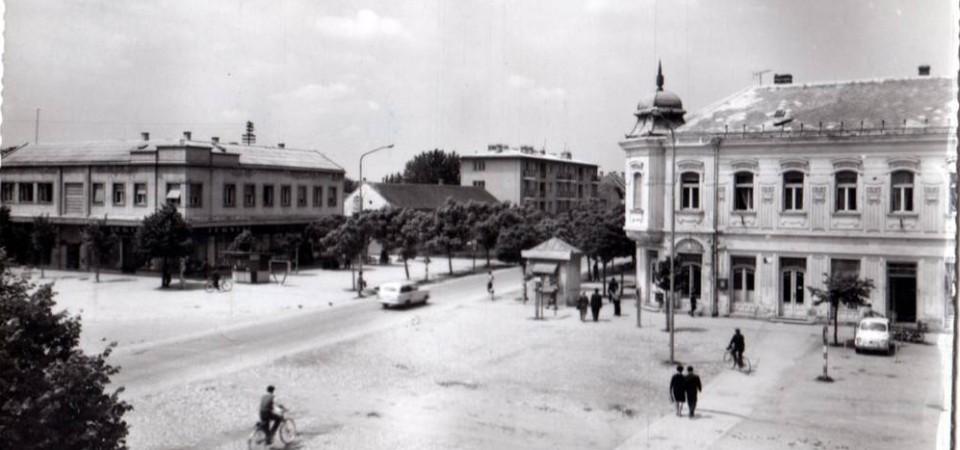 Na staroj fotografiji s druge polovine 20. veka vidi se centar Stare Pazove, štedionica iz 1905.god., kiosk na centru, ljudi,biciklista, automobili, sa leve strane je zgrada firme Cetrosrem,drvored i stambene zgrade.