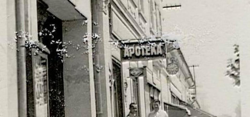 Na staroj fotografiji s druge polovine 20. veka vidi se centar Stare Pazove, dom porodice Lovodić, reklama pazovačkog fotografa Jefte Gambelića, apoteka i dva čoveka ispred zgrade.