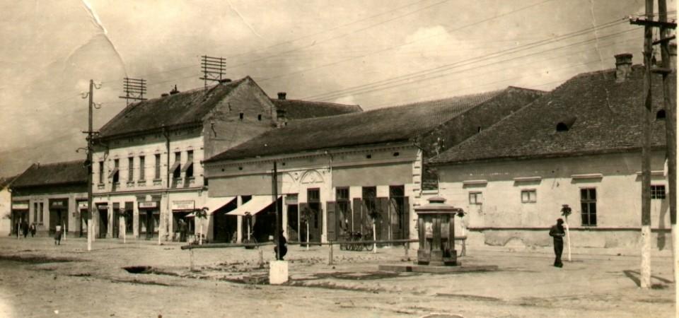 Na staroj fotografiji iz prve polovine 20.veka nalazi se centar Stare Pazove, zgrade, bunar, ljudi, trgovačke radnje itd.