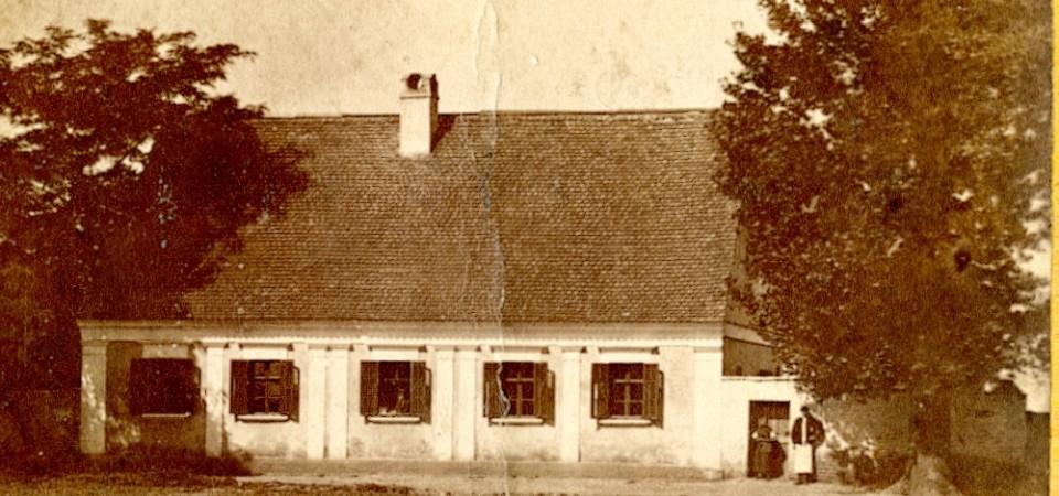 Na staroj fotografiji s druge polovine 19. veka vidi se parohijski dom evangeličke crkve, drveće, muskarac i žena stoje ispred kapije.