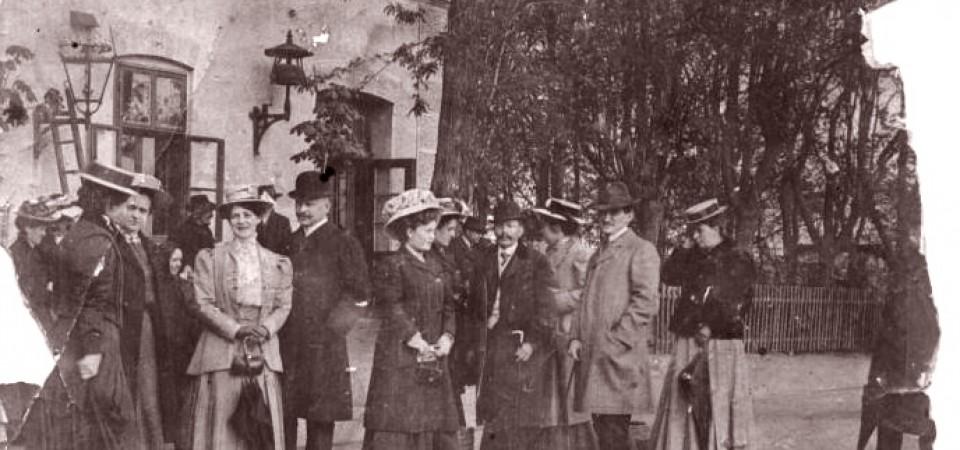 Na staroj fotografiji s druge polovine 19. veka vide se ljudi koji čekaju voz na železničkoj stanici u Staroj Pazovi i zgrada stanice.