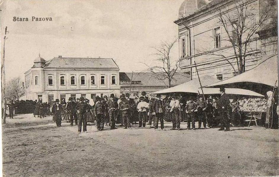 Na razglednici Stare Pazove iz prve polovine 20. veka nalazi se centar Stare Pazove, zgrada hotela Petrović, pijaca i ljudi.