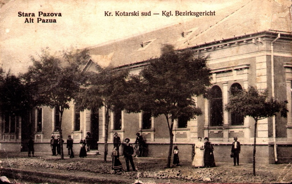 Na razglednici se nalazi zgrada kotarskog suda u Staroj Pazovi a ispred nje su ljudi, drvored, bicikli itd.