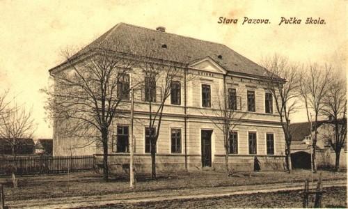 Na staroj razglednici Stare Pazove  iz prve polovine 20.veka nalazi se: nalazi se zgrada Pučke škole, žena, kapija, ograda, drvored bez lišća, put itd.